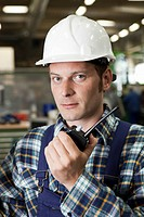 Portrait of a factory worker holding a walkie_talkie
