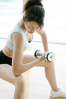 A young woman lifts a dumbbell as she works out in the gym