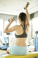 A young woman lifts dumbbells with both hands as she works out in the gym