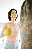 A young woman smiles as she punches the punch bag (thumbnail)