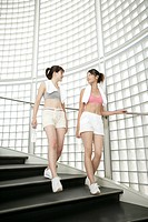 Two young women walk down the stairs after their exercise (thumbnail)