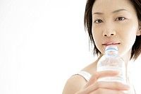 Front view of a young woman drinking water after her exercise