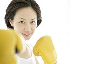 A young woman smiles with the gloves on as she poses against the camera