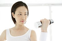 Front view of a young woman lifting the dumbbell