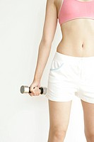 Midsection of a young woman lifting the dumbbell