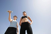 Low angle view of a young woman holding dumbbell as her mate looks on