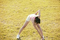 A young woman bends and touches her feet while she exercises amidst grassland