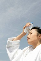 A woman in bathrobe placing a bottle of water on her forehead