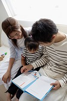 A young couple reading a book to their child