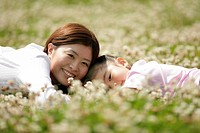 Mother and a daughter lying in a garden amidst flowers