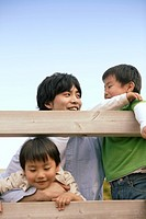 Father enjoys being with his two sons near the wooden planks