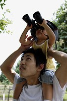 A boy on father's shoulder, looking into binoculars