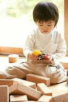 A small boy playing with a toy and some rectangular slabs