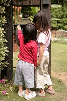 Rear view of two children looking at a metallic structure