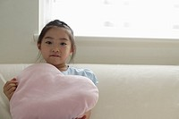 A girl holding a cushion on sofa
