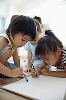Three children drawing pictures
