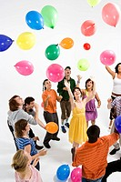 A group of young adults reaching for floating balloons