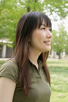 Side view of a young woman standing amidst grassland (thumbnail)