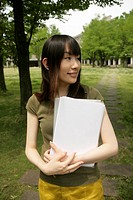 A young woman holds files and papers while she stands amidst grass and trees