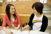 Two young women smile at each other as they sit on a bench inside the class room