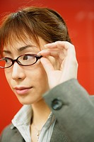 A businesswoman holding her glasses stares at something