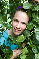 Portrait of a young woman´s face framed by leaves
