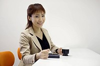 A woman holding a cup of coffee as she smiles at the camera