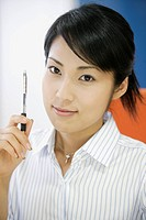 A businesswoman holding a pen smiles at the camera