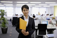 A professional woman holding a file smiles at the camera in the office