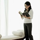 Young woman standing and reading a book