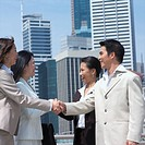 Side profile of a businessman and a businesswoman shaking hands with their colleagues