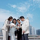 Low angle view of a businessman showing document to three businesswomen (thumbnail)