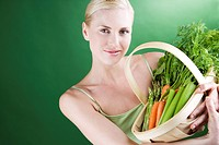 A young woman holding a basket full of vegetables, smiling (thumbnail)