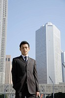 Businessman against office buildings, portrait (thumbnail)
