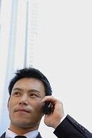 Businessman conversing on a cellphone, close_up