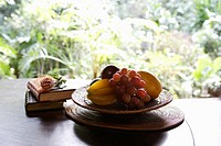 Close_up of fruit and books kept on a table