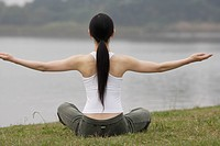 Rear view of a young woman in lotus position (thumbnail)