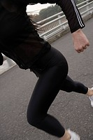 Midsection of a young woman jogging on a road