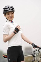 Close_up of a young woman standing near her bicycle