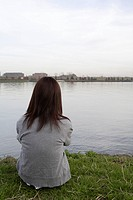 Rear view of a woman sitting near a lake