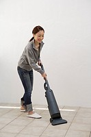 Side view of a young woman cleaning floor with a vacuum cleaner