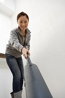 Portrait of a young woman cleaning with a vacuum cleaner (thumbnail)