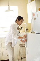 A young woman opening refrigerator in kitchen