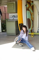 View of a young woman sitting on the skateboard (thumbnail)