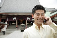 A smiling young man using cellphone