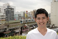A young man smiling with buildings and train in background