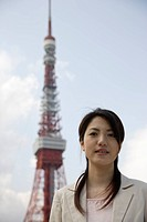 Low angle view of a young woman with tower in background