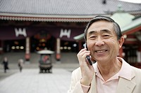 Portrait of a smiling senior man using mobile phone