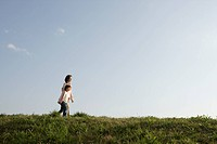 Side view of a mother and daughter walking on grass