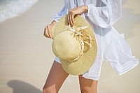A woman standing on beach with hat in hand